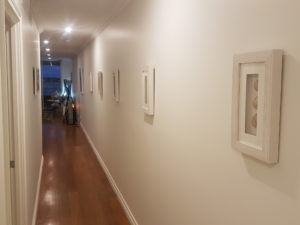 long hallway with timber floor and wall mounted picture frames