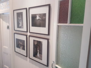 hallway featuring group of four picture frames